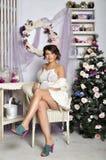 美丽的怀孕的少妇的画象在圣诞树附近的 免版税图库摄影