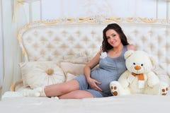 美丽的怀孕的浅黑肤色的男人坐与玩具熊的一张床 免版税图库摄影