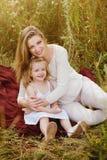 美丽的怀孕的白肤金发的微笑的拥抱母亲和的女儿,家庭价值观,爱 库存图片