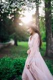 美丽的性婚姻的长的鞋带米黄礼服,在头发的装饰女孩深色的新娘户外,在有树的一个公园, 库存图片