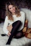 美丽的性感的一件温暖的毛线衣和袜子的甜点微笑的愉快的女孩在卧室坐床 库存照片