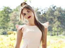 美丽的性感的在公园太阳亮光礼服的妇女深色的步行 库存照片