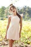 美丽的性感的在公园太阳亮光礼服的妇女深色的步行 库存图片