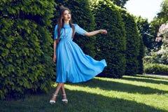 美丽的性感的在公园太阳亮光礼服的妇女深色的步行 免版税库存图片