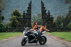 美丽的性感的女孩坐在黑白的一辆摩托车 模型在一黑球衣和牛仔布短裤摆在穿戴了 库存照片