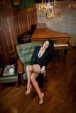 美丽的性感的女孩坐椅子和放松 深色的妇女画象有形成挑战的长的腿的 肉欲的女性 免版税库存照片