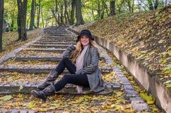 年轻美丽的性感的女孩式样摆在下落的黄色中的秋天公园在老台阶离开在帽子、外套、牛仔裤和b 免版税库存照片