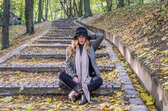 年轻美丽的性感的女孩式样摆在下落的黄色中的秋天公园在老台阶离开在帽子、外套、牛仔裤和b 免版税库存图片