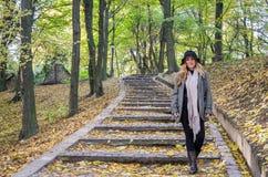 年轻美丽的性感的女孩式样摆在下落的黄色中的秋天公园在老台阶离开在帽子、外套、牛仔裤和b 库存图片