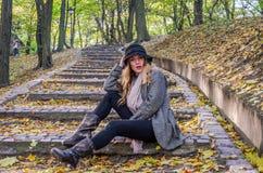 年轻美丽的性感的女孩式样摆在下落的黄色中的秋天公园在老台阶离开在帽子、外套、牛仔裤和b 库存照片