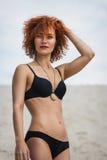 美丽的性感的女孩时尚室外照片有红色头发和被晒黑的皮肤的佩带黑比基尼泳装和辅助部件,放松在夏天 免版税库存照片