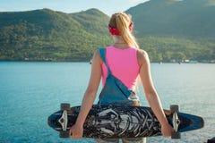 美丽的性感的女孩站立与在海前面的longboard晴朗的天气的 休闲 健康生活方式 库存图片