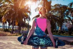 美丽的性感的女孩站立与longboard在晴朗的天气的棕榈附近 休闲 健康生活方式 极其 免版税库存图片