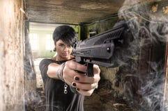 美丽的性感的女孩藏品枪 免版税库存图片
