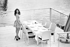 美丽的性感的妇女丝绸礼服深色的海水餐馆 免版税库存照片
