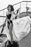 美丽的性感的妇女丝绸礼服深色的海水餐馆 图库摄影