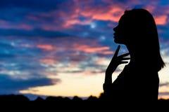 美丽的性感的妇女剪影日落背景的  库存照片