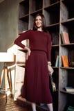美丽的性感的妇女深色的头发时装模特儿穿戴时髦的红色礼服羊毛毛线衣裙子偶然汇集魅力姿势演播室 免版税库存照片
