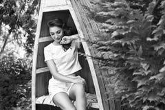 美丽的性感的妇女礼服给深色的构成自然休息穿衣 免版税库存图片