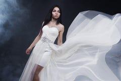 美丽的性感的妇女年轻人 女孩画象长的白色礼服的,神秘,神奇样式,黑暗的背景 免版税库存照片