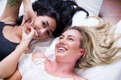 美丽的性感的微笑的女同性恋者恋人在放置在床上的早晨,做与他们头发和深色做的心脏形式 库存图片