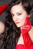 美丽的性感的深色的妇女画象有长的头发的在红色 免版税库存照片
