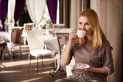 美丽的性感的白肤金发的女商人餐馆饮料咖啡茶 免版税库存照片
