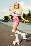 美丽的性感的白肤金发的女孩摆在桃红色短裤的葡萄酒溜冰鞋的和在冰鞋的白色T恤杉在一个温暖的夏天e停放 图库摄影