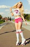 美丽的性感的白肤金发的女孩摆在桃红色短裤的葡萄酒溜冰鞋的和在冰鞋的白色T恤杉在一个温暖的夏天e停放 免版税库存照片