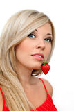 美丽的性感的白肤金发的女孩用红色草莓 免版税库存照片
