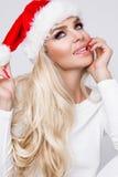 美丽的性感的白肤金发的女性式样作为一个红色盖帽的圣诞老人打扮的母亲和女儿 免版税库存图片