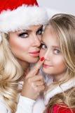 美丽的性感的白肤金发的女性式样作为一个红色盖帽的圣诞老人打扮的母亲和女儿 库存照片