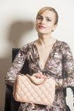 美丽的性感的白肤金发的妇女坐椅子 免版税库存图片