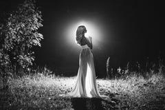美丽的性感的白肤金发的白色束腰和黑裙子 免版税库存图片