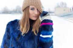 美丽的性感的逗人喜爱的快乐的愉快的女孩拉扯了与明亮的构成的帽子闪光在眼睛与明亮的蓝色外套明亮的冬日 免版税库存图片