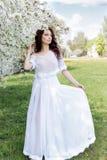 美丽的性感的逗人喜爱的柔和的女孩在明亮的夏日一个开花的庭院的一件轻的白色礼服走  免版税库存图片