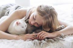 美丽的性感的金发碧眼的女人在窗口说谎与猫一起 库存图片