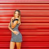 美丽的性感的年轻白肤金发的妇女摆在红色墙壁后的-警察 图库摄影