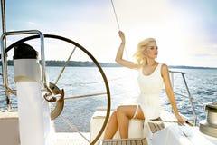 美丽的性感的年轻白肤金发的妇女,乘坐小船在水,日程,美好的构成,衣物,夏天,太阳,完善的身体fi 免版税库存照片