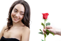美丽的恼怒的女孩接受一朵红色玫瑰 她惊奇,看花和微笑 免版税库存照片