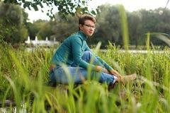 美丽的情感女孩坐在草和wate中的一个湖 免版税图库摄影