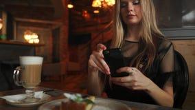 美丽的情感愉快的女孩做照片在咖啡馆,在桌上的拿铁,点心冰淇淋巧克力蛋糕的食物 股票录像