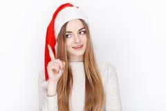美丽的情感白肤金发的女性式样穿戴圣诞老人帽子 圣诞节和新年好问候概念 图库摄影