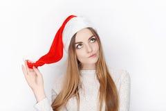 美丽的情感白肤金发的女性式样穿戴圣诞老人帽子 圣诞节和新年好问候概念 免版税库存图片