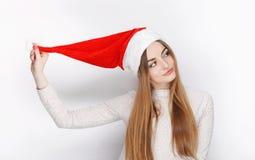 美丽的情感白肤金发的女性式样穿戴圣诞老人帽子 圣诞节和新年好问候概念 免版税库存照片