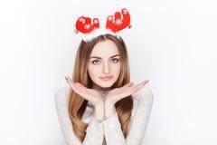 美丽的情感白肤金发的女性式样穿戴圣诞老人鹿戴头受话器 背景圣诞节概念问候查出白色 库存图片