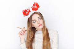 美丽的情感白肤金发的女性式样穿戴圣诞老人鹿戴头受话器 背景圣诞节概念问候查出白色 免版税库存照片