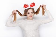 美丽的情感白肤金发的女性式样穿戴圣诞老人鹿戴头受话器 背景圣诞节概念问候查出白色 免版税库存图片