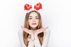 美丽的情感白肤金发的女性式样穿戴圣诞老人鹿戴头受话器 背景圣诞节概念问候查出白色 库存照片