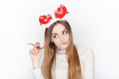 美丽的情感白肤金发的女性式样穿戴圣诞老人鹿戴头受话器 背景圣诞节概念问候查出白色 图库摄影